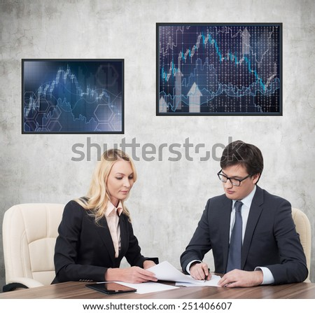 two businesspeople working in office with charts on plasma panel - stock photo