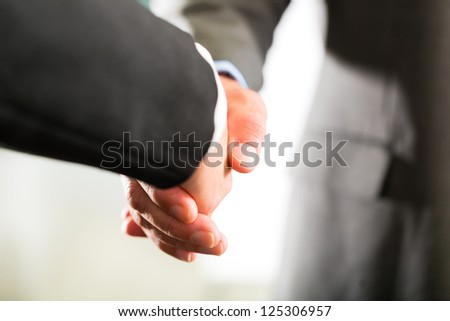 Two businesspoeple shaking hands closing a deal, closeup - stock photo