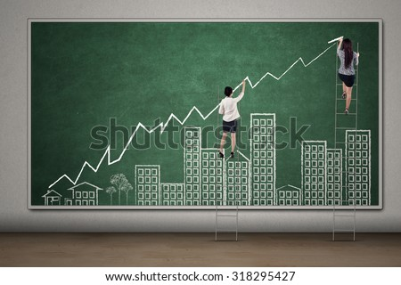 Two businesswoman draw increasing business property graph on the chalkboard with building and growing arrow - stock photo