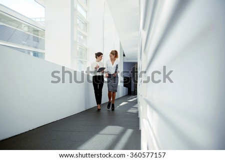 Two businesswoman dressed in formal wear laughing at funny video on digital tablet during work break, young attractive female holding touch pad and talking about something cheerful to her partner - stock photo