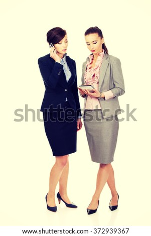 Two businesswomans discussing with eachother. - stock photo