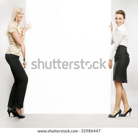 Two businesswomen carrying a white board - stock photo