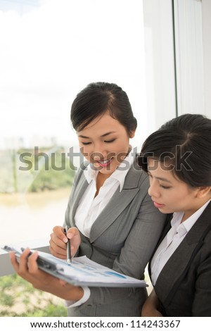 Two businesswomen discussing financial charts - stock photo