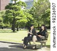 Two businesswomen eating lunch in park - stock photo