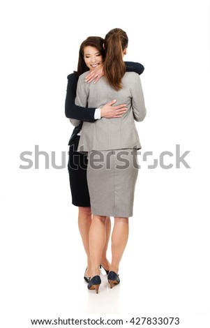 Two businesswomen embracing each other. - stock photo