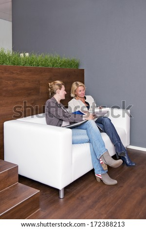 Two businesswomen going over notes together during an informal business meeting on a couch - stock photo