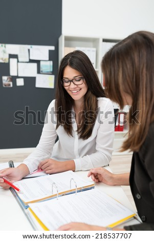Two Businesswomen Looking at Notes in Meeting - stock photo
