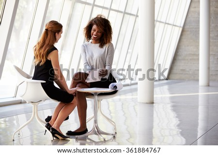 Two Businesswomen Meeting In Reception Of Modern Office - stock photo