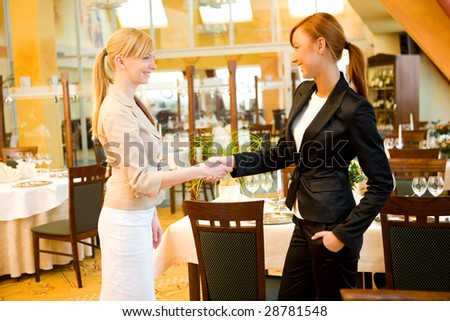 Two  businesswomen shake hands and conclude a deal. They're in restaurant. - stock photo