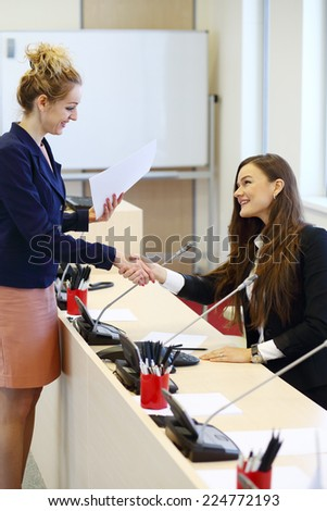 Two businesswomen shaking hands at conference hall - stock photo