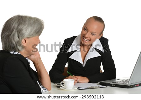 Two businesswomen sitting at the table with coffee and laptop - stock photo