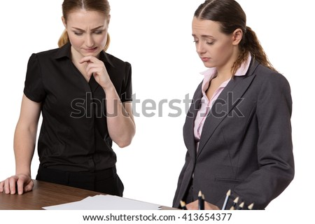 Two businesswomen standing at an office desk having meeting and discussing paperwork.  - stock photo