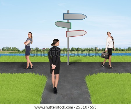 Two businesswomen standing at sign of right and left side and one of them back to camera - stock photo