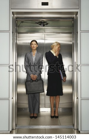 Two businesswomen standing together in office elevator - stock photo