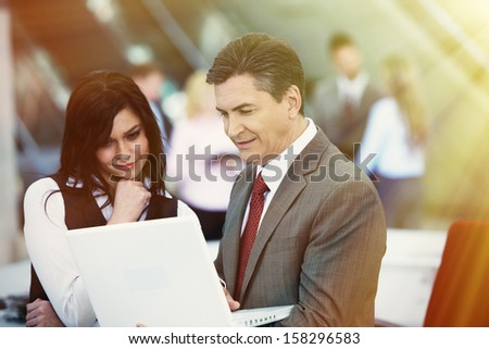 Two bussiness partners man and woman over team background - stock photo
