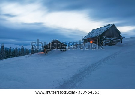 two cabins in winter mountain in the evening - stock photo