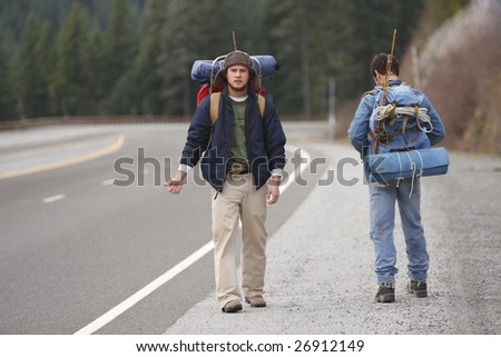Two campers hitchhiking on a mountain road. - stock photo