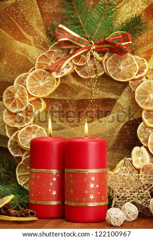 Two candles and christmas decorations, on golden background - stock photo