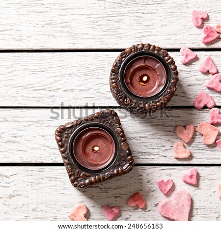 Two candles on white wood table with heap of small hearts. Top view. - stock photo