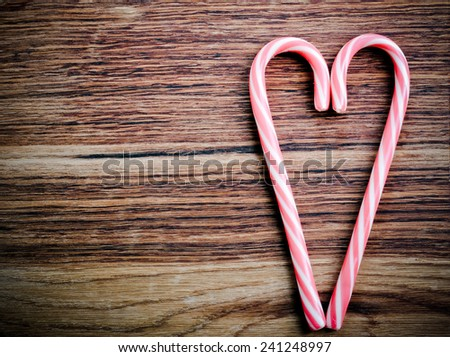 Two candy canes in heart shape over wooden surface - stock photo