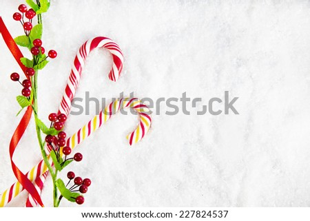Two Candy Canes With Christmas Decoration On Snowy Background. Copy Space - stock photo