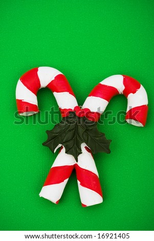 Two candy canes with leaves and holly berries on green background, Christmas background - stock photo