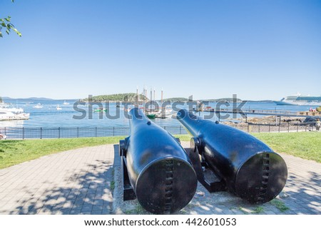Two cannons aimed at sailboats in Bar Harbor Maine - stock photo