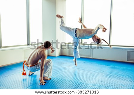 Two capoeira performers showing technical skill while dancing in a fight club - stock photo