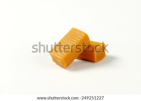 two caramel toffee candies on white background - stock photo