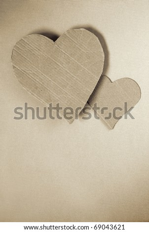 Two cardboard hearts over wrapping paper sheet - stock photo