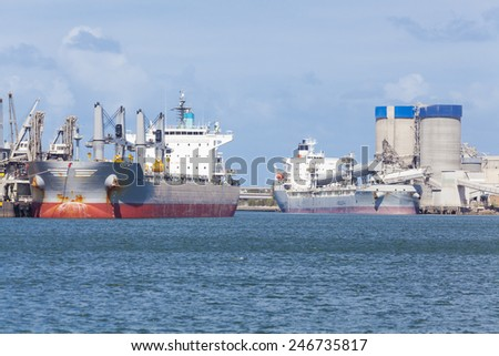 Two cargo ships unloading at a port - stock photo