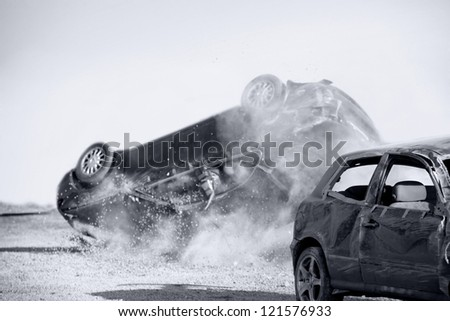 two cars turned upside-down after road collision, monohromatic - stock photo