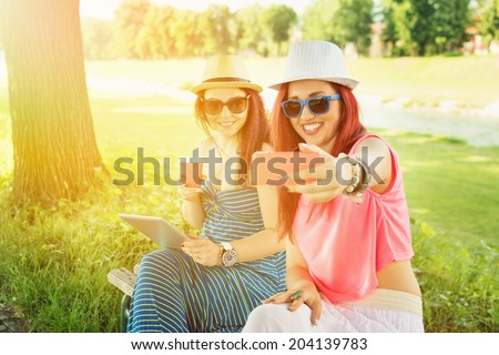 Two casual happy Caucasian teenage girls taking a selfie in park on sunny summer day. Two young women with hats and sunglasses enjoying outdoors in park taking a self portrait with smartphone. - stock photo