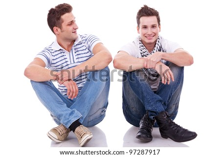 two casual men sitting on a white background. one looking at the camera and the other looking at his friend - stock photo