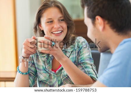 Two casual students having a cup of coffee in college canteen - stock photo