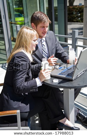 Two caucasian business people having a discussion during lunch hour - stock photo