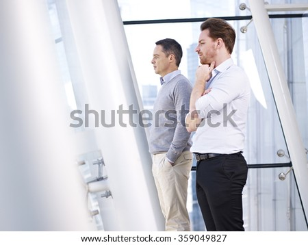 two caucasian business people looking out of window in modern office building. - stock photo