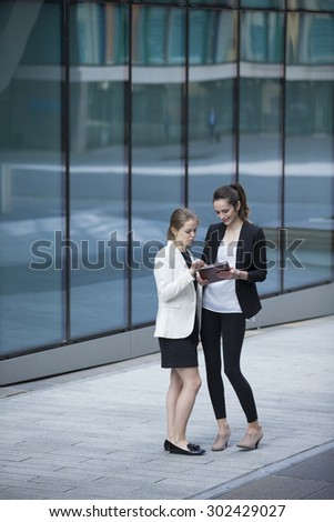 Two Caucasian Business women using digital tablet computer. Full length image. Standing outside a modern office building. - stock photo