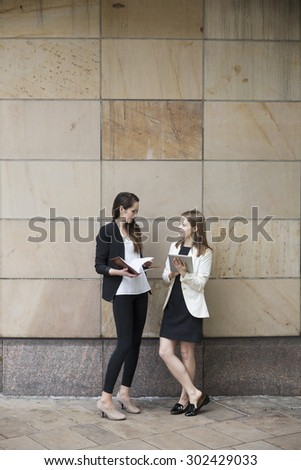 Two Caucasian Business women using digital tablet computer, leaning against a wall. - stock photo