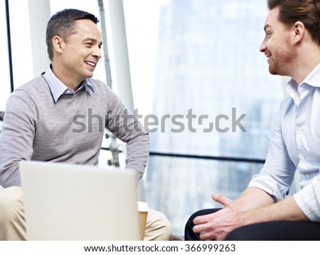 two caucasian businessmen chatting during coffee break in office. - stock photo