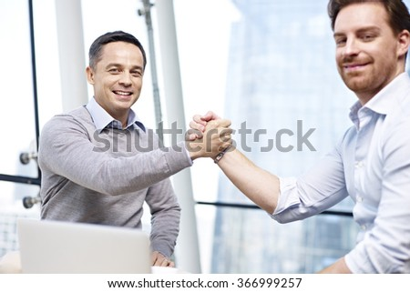 two caucasian businesspeople celebrating success in partnership in office. - stock photo