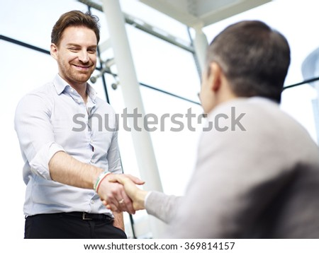 two caucasian businessperson greeting each other by shaking hands in modern office. - stock photo
