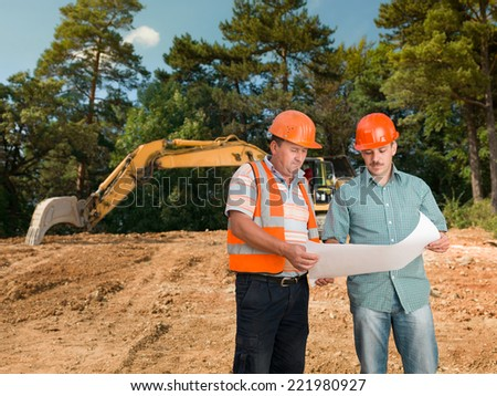 two caucasian engineers on construction site looking at plan and discussing it - stock photo