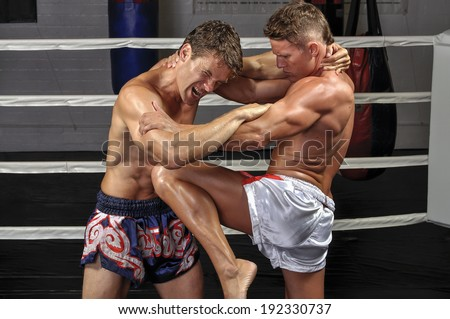 Two Caucasian Muay Thai fighters lock up in the ring during match and one delivers powerful knee to the mid-section - stock photo