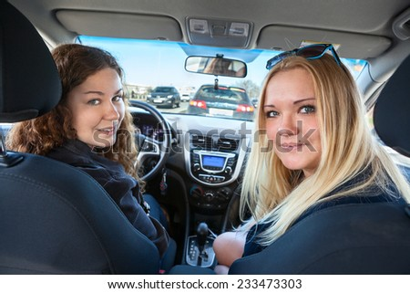 Two Caucasian women sitting inside of car when driving, looking back - stock photo