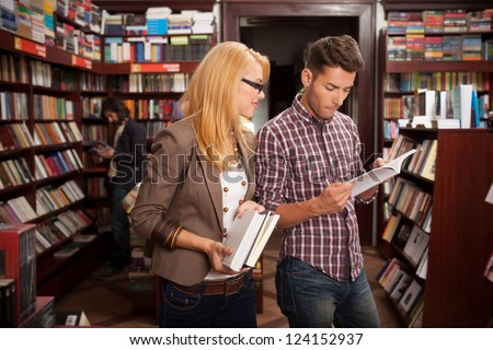 two caucasian young people in a bookstore reading something in a book with many bookshelves in the background - stock photo