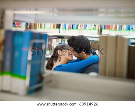 two caucasina students hugging and kissing behind shelves in library. Horizontal shape, side view, copy space - stock photo