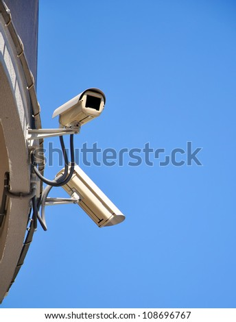 Two CCTV security cameras and blue sky - stock photo