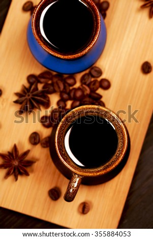 Two ceramics cups of coffee standing on  wooden board with coffee beans and star anise. - stock photo