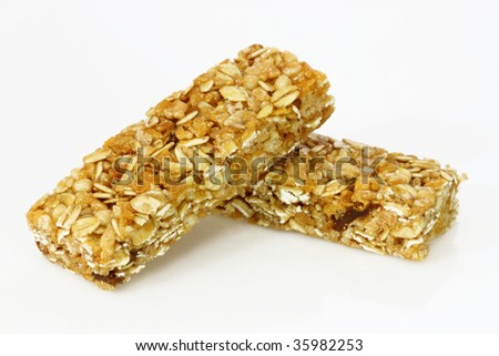 Two cereal bars on a bright background - stock photo